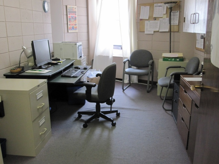 The old, stained and worn carpeting in Htee's office.